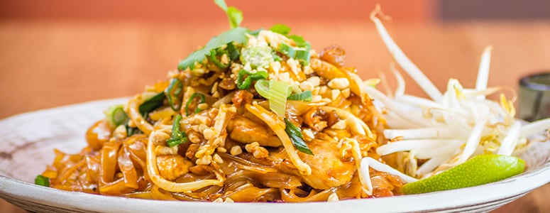 Pad Thai made with tofu topped with bean sprouts and scallions.